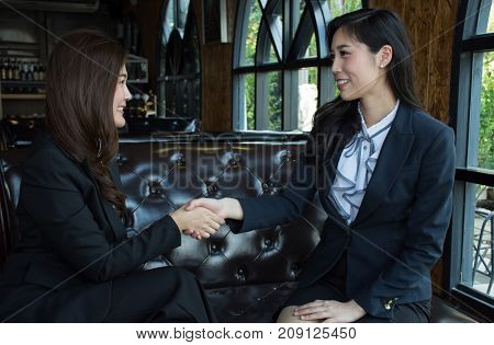 Two confident Asian business woman shaking hands during a meeting in the office, success, dealing, greeting and partner concept