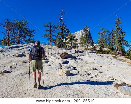 Lone Man Hiking in Sierra Nevada Mountains of California on Granite Hill with Poles and Backpack