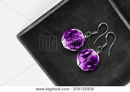 Purple faceted crystal earrings in black jewel box closeup