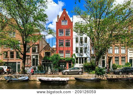 Traditional dutch houses and boats on canal in the most romantic city. Tranquil scene of Amsterdam street in summer. Urban landscape with typical architecture of the old buildings, the Netherlands.