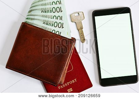 Wallet with a stack of european currency money passport door key and a smartphone with blank screen - mobile application for accommodation or real estate rentals and deals searching. Top view.