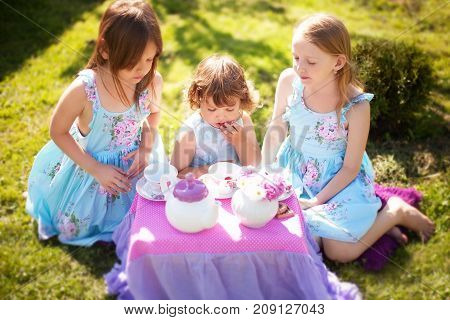 Adorable three little sisters girls dressed like princesses playing tea party. Beautiful decorated tea party outdoors at the backyard.
