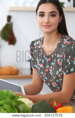 Young hispanic  woman is making online shopping by tablet computer and credit card. Housewife found new recipe for  cooking in a kitchen