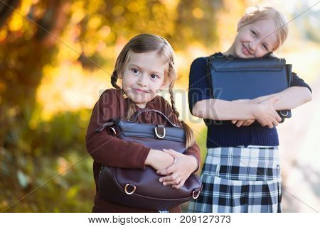 Adorable old-fashioned happy little 6 years old and 10 years old girls reading and smiling back to school chalkboard. Preschooler and schoolgirl sisters schoolkids. Horizontal photo.