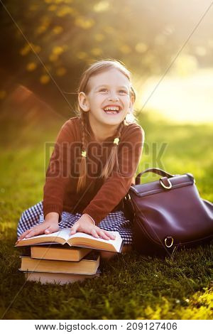Adorable happy old-fashioned little girl wearing school uniform. Smiling holding school bag and pile of schoolbooks sitting on a grass in a sunset light laughing reading. doing homework and having fun. Preschooler girl is happy back to school. Warm autumn