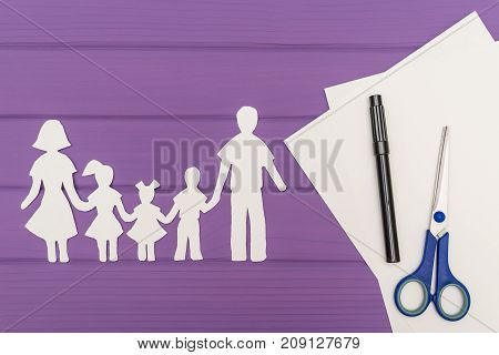 The silhouettes cut out of paper of man and woman with two girls and boy, scissors and marker near on a white sheet of paper on purple wooden background. Concept of family love