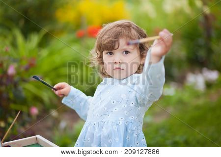 Cute toddler girl painting on the easel in the garden and having fun. Closeup portret. Talented kids. Early art education.