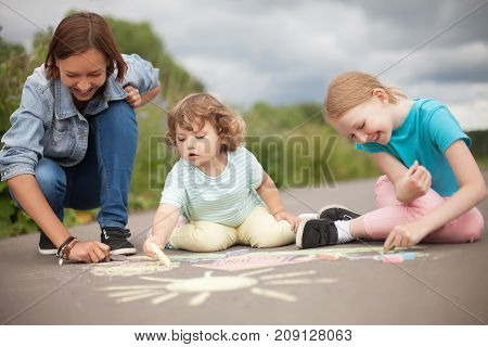 Little girls chalking at the asphalt with elder sister or nanny. Sisters friendship caring elder sister. Best friends children happy family. Drawing with color chalk. Sunny summer days. Happy childhood. Kids in kindergarten. Preschooler leisure time. Kids