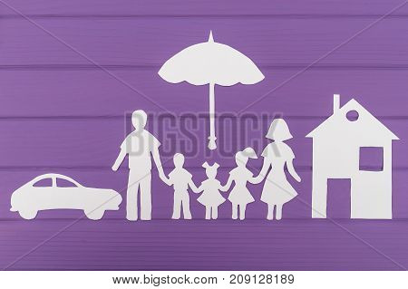 The silhouettes cut out of paper of man and woman with two girls and boy under the umbrella, house and car near on purple wooden background. Concept of family protection