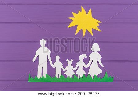The silhouettes cut out of paper of man and woman with two girls and boy on the grass under the sun on purple wooden background. Concept of family unity