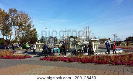 Gdynia, Poland - October 15, 2017: Fountain on the Kosciuszko Square in Gdynia, Poland. People stand at the fountain in the   center of Gdynia.