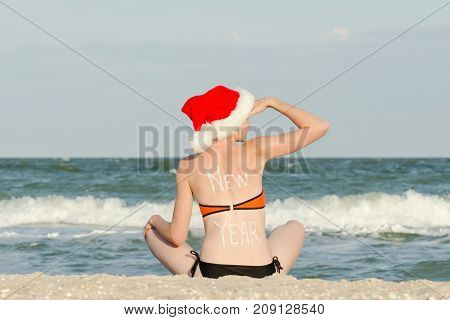 Girl In Santa Hat With The Inscription New Year On The Back Is Sitting On The Beach And Looks Into T