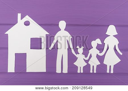 The silhouettes cut out of paper of man and woman with two girls, house near on purple wooden background. Concept of family protection