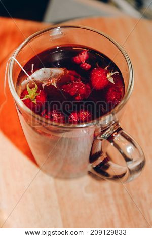 Raspberry tea, tea bag. Red fruit tea, hot energy drink in glass mug. Teatime, pastime, cozy atmosphere in home, cafe, cafeteria in cold weather. Traditional black tea with herbs and berries.5 o'clock