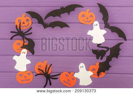 Halloween silhouettes cut out of paper made of round frame with pumpkins, bats, cat, spider, hat and ghosts on purple board. Halloween holiday. Copy space