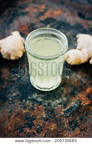 ginger juice in small glass jar with ginger root behind