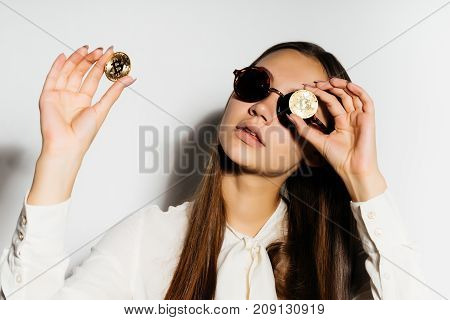 electronic money. The girl in glasses and with gold coins. Money, wealth. Bitcoins