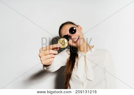 a gold coin close-up. the girl in glasses shows a coin. Money, electronic money, crypto currency