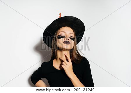 a witch girl with black lips, a steep black suit and a hat with autumn leaves and pachy on her face. The witch was going to the Halloween party.
