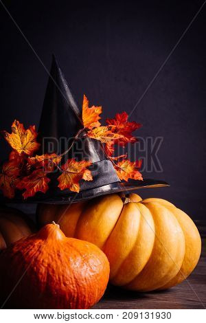 autumn holiday, a large pumpkin, candles, dry grass, Halloween, a mesmerizing picture. A large witch hat with autumn leaves lies on the dumpling.
