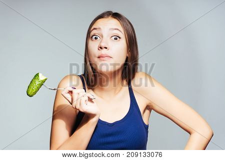 a girl with a sports body eating a cucumber with an outraged look and looking directly at the camera.