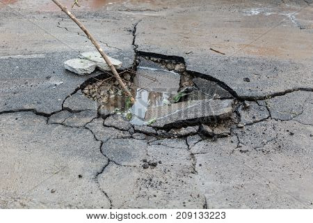A Hole In The Asphalt In The Courtyard Of A Residential Area. Damaged Road