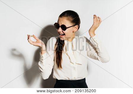 a happy girl in a white blouse and wearing glasses holds a coin in her hands and laughs, electronic money, bitcoins, crypto currency.
