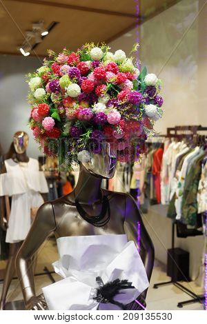 Female mannequin with many bright flowers in head in shop center