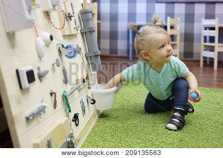 Little girl plays on green carpet with busy board in modern kindergarten