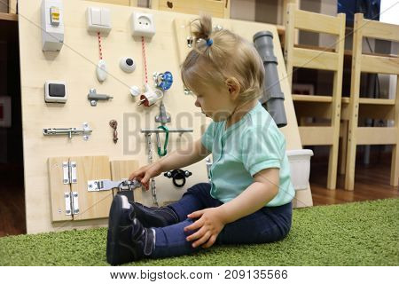Little girl plays on carpet with busy board in modern kindergarten