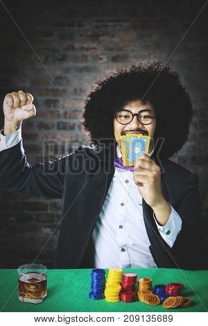 Young man winning the gambling while holding his card and a glass of beer on the table