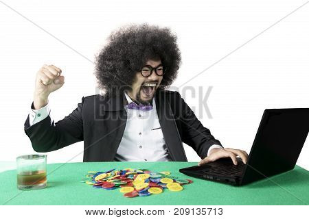 Portrait of happy Afro man winning an online poker while raising hand isolated on white background