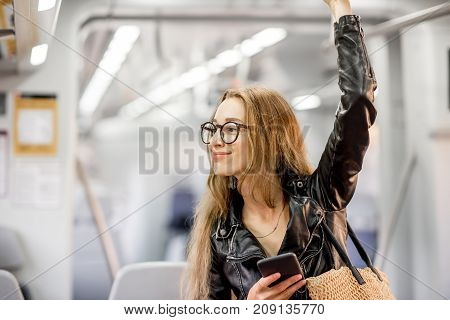 Lifestyle portrait of a young businesswoman standing with smart phone at the modern train