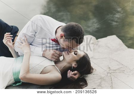 beautiful loving couple kissing by the lake