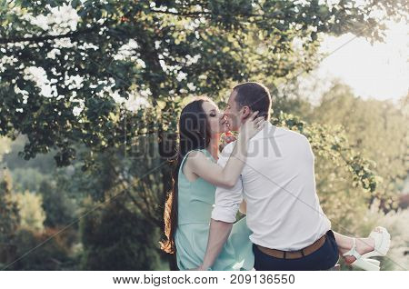 Lovers kiss at sunset near a tree