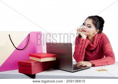 Image of beautiful woman shopping online by using a laptop while daydreaming in the studio