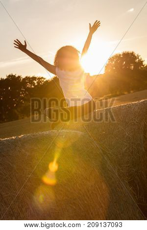 Mixed race African American girl teenager female young woman sitting on hay bale arms raised celebrating in sunset or sunrise golden evening or morning sunshine