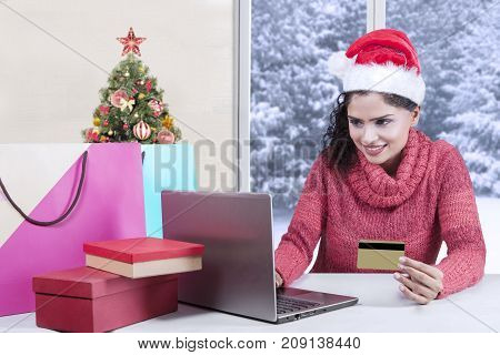 Pretty girl using a laptop while holding a credit card for shopping online and sitting at home