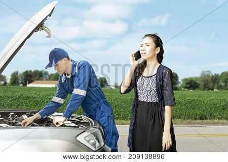 Image of young mechanic is checking broken car while standing with his panicky customer on the roadside