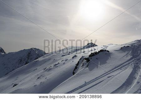 Mountain Panorama With Snow, Ski Tracks, Sun And Summit Cross In Winter In Stubai Alps, Austria