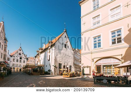 Tallinn, Estonia. People Resting In Street Cafe Restaurant And Walking In Old Town Under Facades Of Buildings. Tourists Walking Near Town Hall Square In Sunny Summer Day With Blue Sky