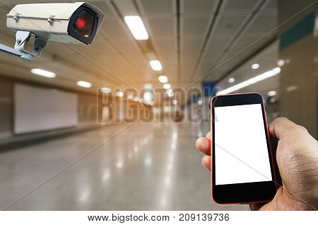 hand using mobile phone with blank screen and security camera system operating with blurred image of subway train station or airport internet surveillance security and safety technology concept