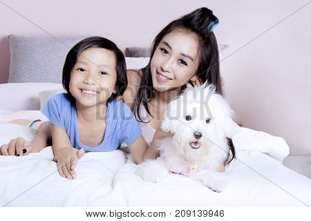 Happy little girl with her mother and Maltese dog lying together on the bedroom and smiling happy
