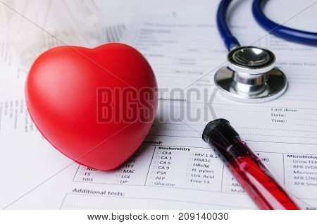 close up of red heart stethoscope laboratory test tube and medical form on desk blood test heart disease medical diagnosis medical report record and history patient concept selective soft focus