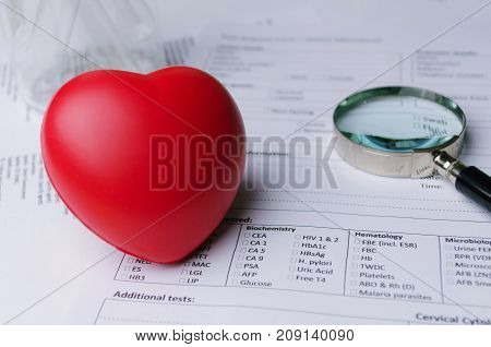 close up of red heart magnifying glass and medical form on desk heart attack heart disease medical diagnosis medical report record and history patient concept selective soft focus