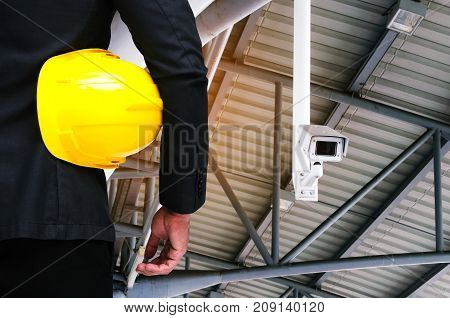 back view of engineer and holding yellow safety helmet standing with CCTV security camera system operating under roof background industrial surveillance security and safety technology concept