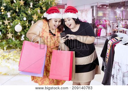 Picture of two fat women wearing Santa Claus hat while using a mobile phone and holding shopping bags in the mall