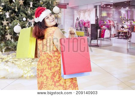 Picture of fat woman looks happy while wearing Santa Claus hat and holding shopping bags in the mall