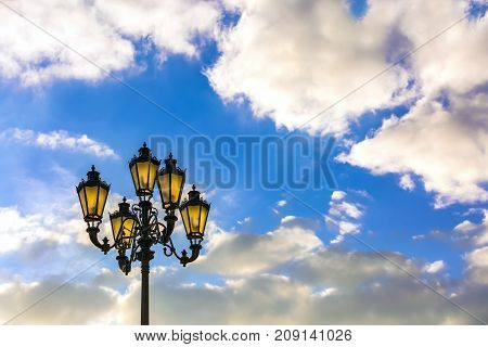 Street black lamppost Pushkin with a lamp made of cast iron against a background of a sunny blue sky with white clouds. City lamppost, Moscow, Russia.