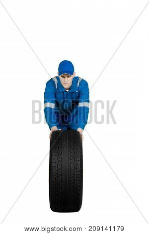 Portrait of European male mechanic pushing a tire in the studio isolated on white background